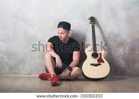 Man in denim shorts sitting next to a guitar on the wall background in style grunge, music, musician, hobby, lifestyle, hobby