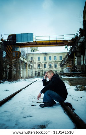 Man in depression sitting on rail in factory - stock photo