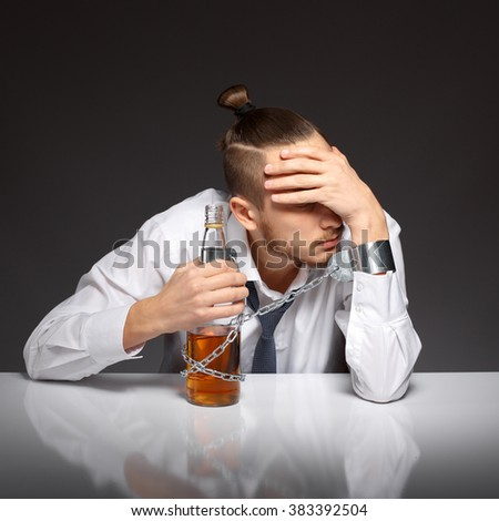 Man in despair of alcohol addiction holding his head. Addicted to alcohol, alcoholism concept, social problem - stock photo