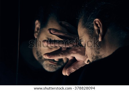 Man in despair, sad and lonely resting his head on a hand, in front of mirror - stock photo