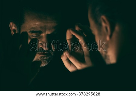 Man in despair with raised hands and bowed head, in a low light room looking at his reflection in front of mirror