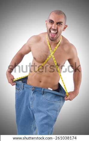 Man in dieting concept with oversized jeans - stock photo
