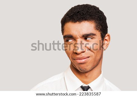 Man in disbelief.  Close-up portrait of young Afro-American man showing the disgust on his face while standing against grey background