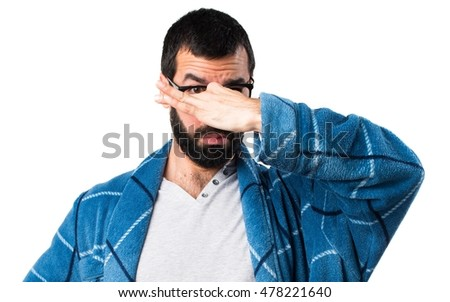 Man in dressing gown making smelling bad gesture