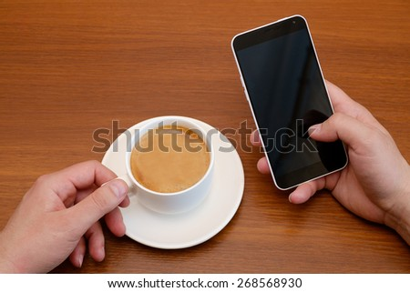 Man in drinking espresso coffee and looking smartphone - stock photo