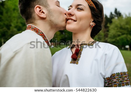 Man in embroidered shirt kisses woman in ethnic clothes in a cheek