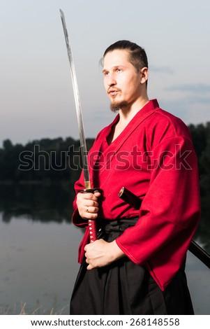 Man in ethnic samurai japanese clothing uniform with katana sword portrait - stock photo