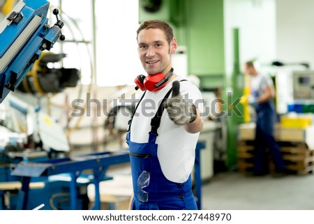 man in factory with thumb up - stock photo