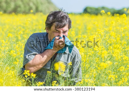 man in field blowing his nose and suffering from hay fever.  - stock photo