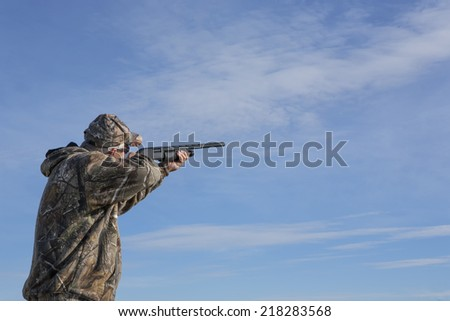 Man in field hunting aiming up into the sky with shot gun - stock photo