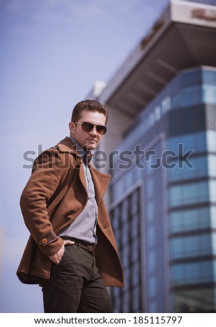 man in front of a glass building wearing coat