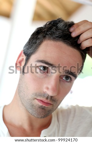 Man in front of mirrror looking at his hair - stock photo