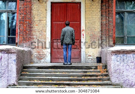 Man in Front of the Old House before the Closed Door - stock photo