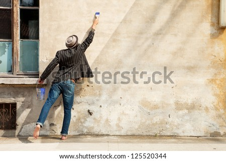 man in front of the wall with brush - stock photo