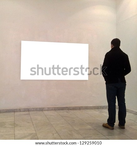 Man in gallery room looking at empty frames - stock photo