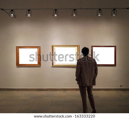 Man in gallery room looking at empty picture frames - stock photo