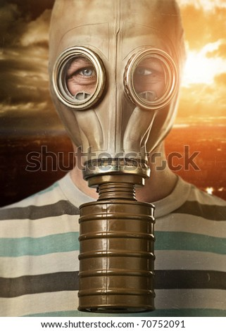 Man in gas mask against urban background - stock photo