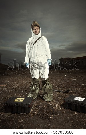 Man in gas mask and overall - stock photo