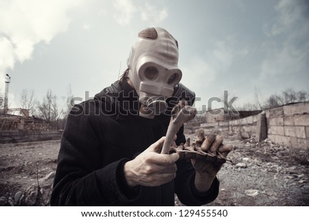 Man in gas mask holding residual bones after doomsday - stock photo