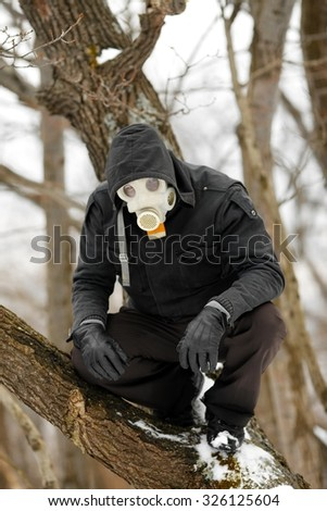 Man in Gas Mask lurking in the forest - stock photo