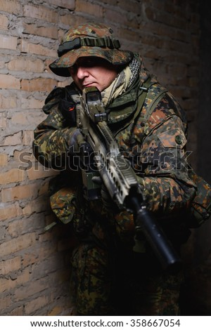 Man in German uniform standing in dark room with automatic rifle with silencer and collimator sight/Armed man with automatic rifle with silencer