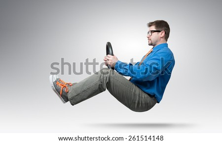 Man in glasses car driver with a wheel - stock photo