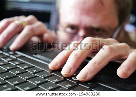 Man in glasses furtively or secretly typing on a laptop keyboard - stock photo