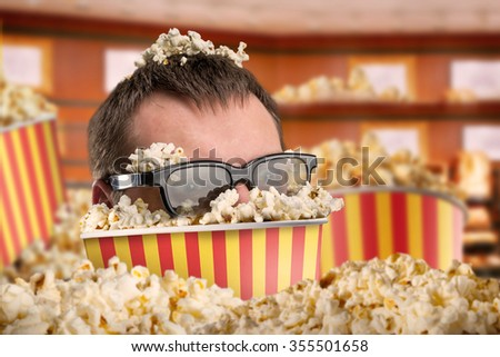 Man in glasses in a bucket of popcorn - stock photo