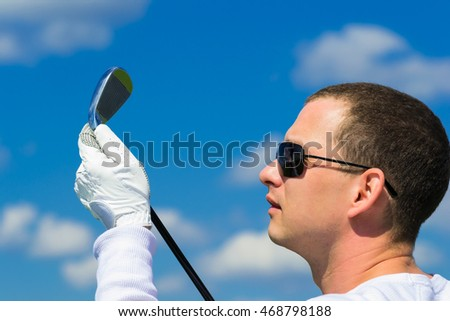 man in glasses looks at the stick