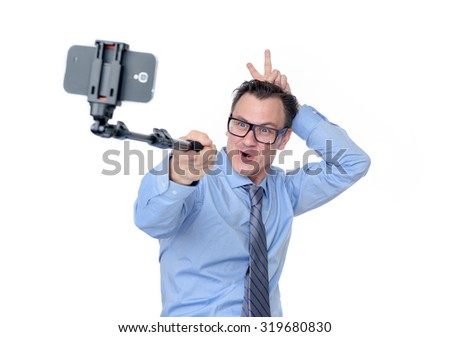 Man in glasses making selfie with a stick, isolated on white background  - stock photo