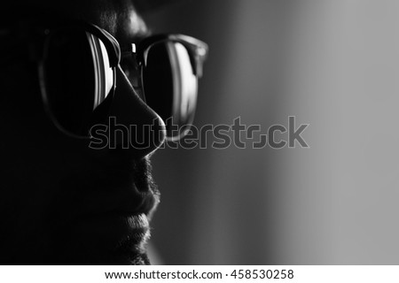 man in glasses on dark background, portrait, black and white photo.