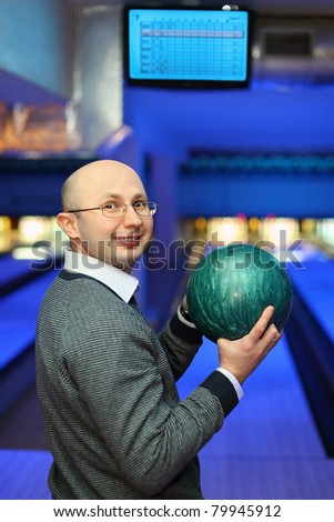 Man in glasses stands sideways and holds  ball for bowling - stock photo