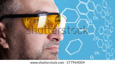man in glasses working on a blue background - stock photo