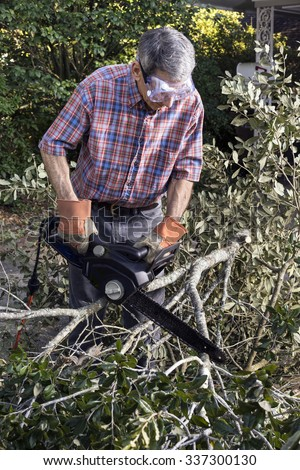 Man in gloves and safety goggles cutting fallen branches and foliage debris after a storm; closeup.