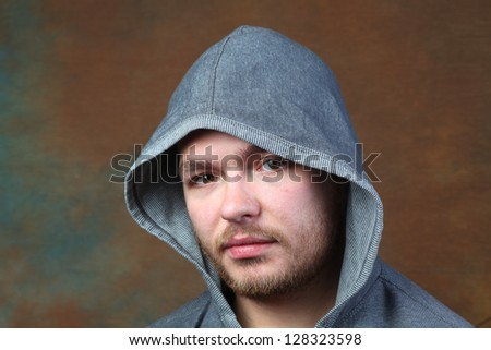 Man in Gray Hoodie/headshot of lightly bearded man wearing gray hoodie against brown portrait background