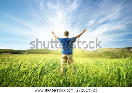 Man in green meadow of wheat. Emotional scene.