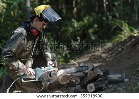 Man in green overall working with an electric chainsaw cutting into log. Shallow focus, sawdust flying around work area. Some cut up logs can be seen near work area.  - stock photo
