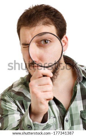 Man in green shirt looking through a magnifying glass. White background.