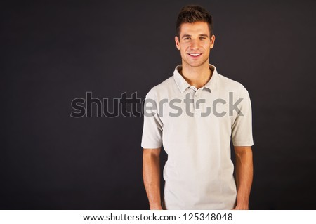 Man in grey polo t-shirt on black background with smile - stock photo