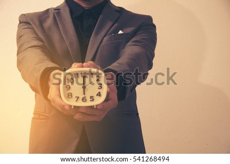 Man in grey suit hold a white clock by two hand in room.