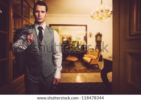 Man in grey waistcoat with briefcase in luxury home interior - stock photo