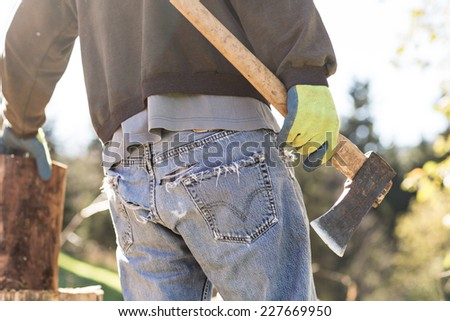 Man in grunge blue jeans chopping wood with vintage axe. Color toned image.  - stock photo
