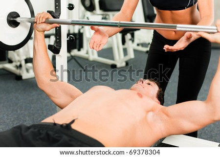 man in gym with personal fitness trainer exercising power gymnastics with a barbell - stock photo