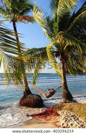 Man in hammock on the beach - stock photo