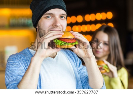 Man in hands holds a burger. Man eating a burger at the cafe