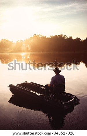 Man in hat sitting in small fishing boat on lake river water pond at sunrise sunset dawn early with sun rays and trees forest on horizon feeling peaceful relaxed serene calm meditative lonely alone - stock photo