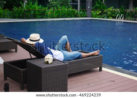 Man In Hat Sunbathing On Deck Chairs Next To A Swimming Pool