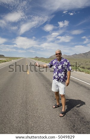 Man in Hawaiian shirt hitchhiking on  desert highway under beautiful blue with clouds sky