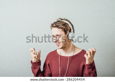Man in headphones listening to music. On a gray background. - stock photo