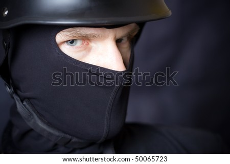 Man in helmet and mask staring at you over dark background